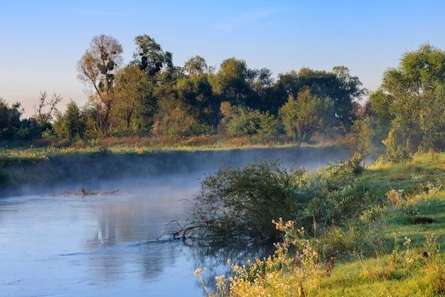 Mgła nad powierzchnią rzeki o wschodzie słońca w letni poranek. krajobraz rzeki