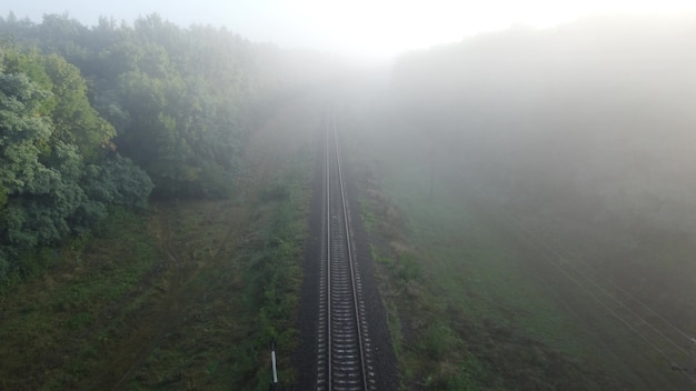 Mgła nad torami kolejowymi. poranny jesienny krajobraz, tory po których jeżdżą pociągi.