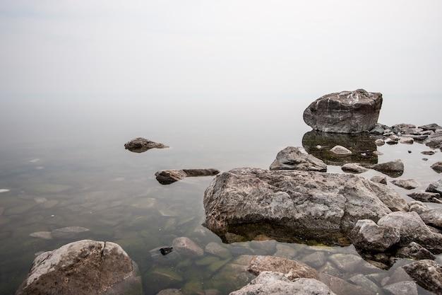 Mgła nad wodą na jeziorze z dużymi kamieniami. czysta woda z zielonymi kamieniami. tło białe mleko. skopiuj miejsce na górze.