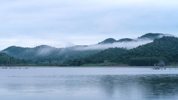 Mgła we wczesnych godzinach porannych nad jeziorem górskim wcześnie rano.