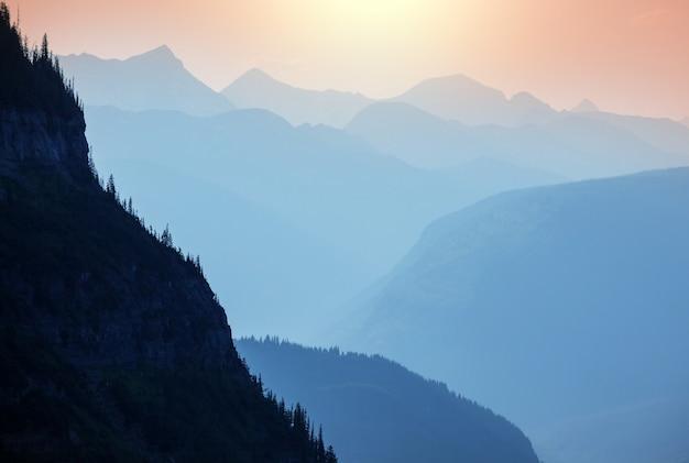 Mglista góra sylwetka o wschodzie słońca