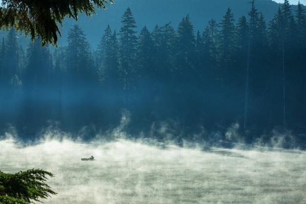 Mgliste górskie jezioro we wczesnych godzinach porannych w górach.