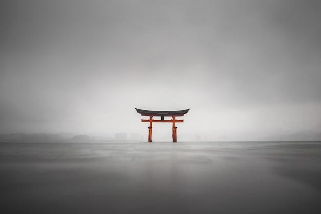 Mgliste ujęcie pływających torii miyajima w japonii podczas deszczu