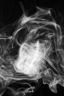 Mglisty biały dym na ciemnym tle