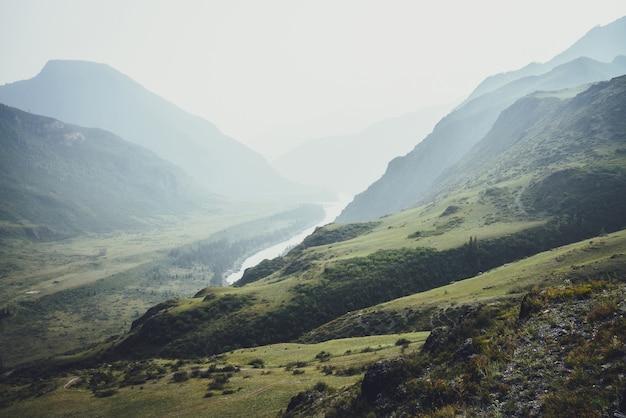Mglisty górski krajobraz ze wzgórzami i skałami na tle szerokiej górskiej rzeki we mgle. klimatyczna sceneria z górską rzeźbą i dużą rzeką w ciemnozielonej dolinie w deszczową pogodę. ponura pogoda