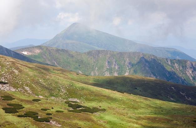 Mglisty letni krajobraz górski i śnieg na zboczu góry (ukraina, karpaty, czarnogóra, goverla)