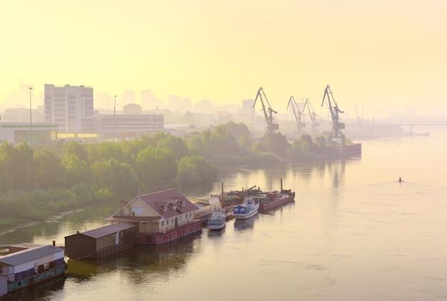 Mglisty poranek nad rzeką ob w nowosybirsku przystań i statki na spokojnej tafli wody