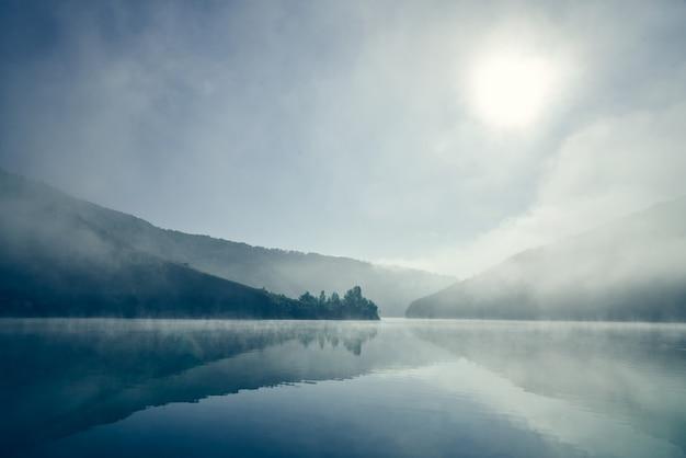 Mglisty wschód słońca nad jeziorem.