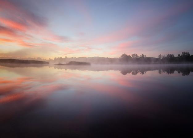 Mglisty wschód słońca nad rzeką, złotogodzinne niebo, mgła nad rzeką