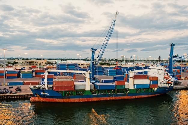Miami, stany zjednoczone ameryki - 01 marca 2016: statek towarowy w morskim porcie kontenerowym z kontenerami i dźwigami. port lub terminal na zachmurzonym niebie. koncepcja logistyki i dostawy towarów frachtowych.