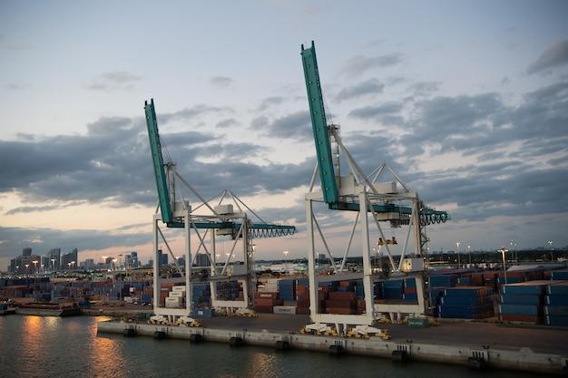 Miami, usa - 01 marca 2016: dźwigi towarowe na zachmurzonym niebie. kontenery w porcie cargo. sprzęt do załadunku ładunków na nabrzeżu. wysyłka ładunków. wieczorem panoramę miasta.