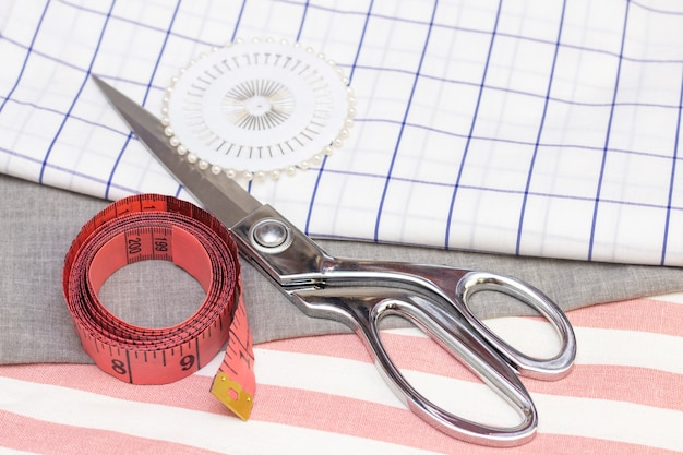 Miara i nożyczki znajdują się na tkaninie bawełnianej. koncepcja szycia, szycie z naturalnych tkanin.