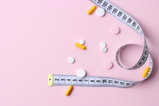 Miara zwijana i tabletki odchudzające na kolorowym tle zbliżenia