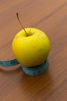 Miara zwijana i zielone jabłko na drewnianym stole. pojęcie diety i zdrowego stylu życia