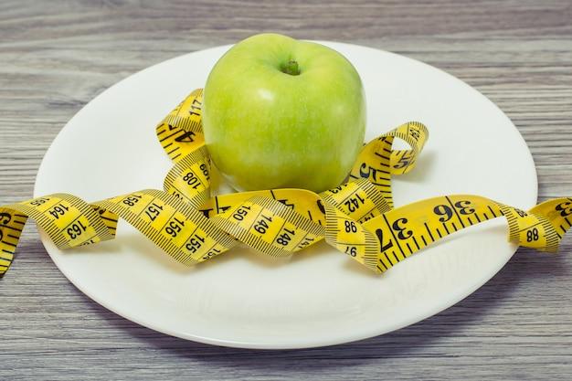 Miara zwijana wokół jabłka na białym talerzu