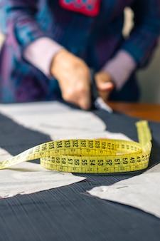 Miara zwijana z krawcowym cięciem tkaniny z nożyczkami w tle. selektywne skupienie się na mierzeniu taśmy na pierwszym planie