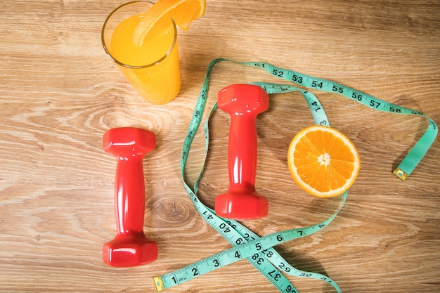 Miarka, hantle, sok pomarańczowy i pomarańczowy na stole