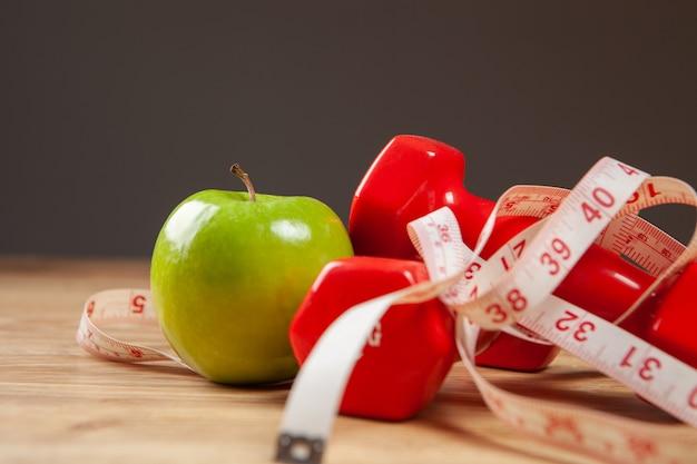 Miarka, jabłko i hantle na stole