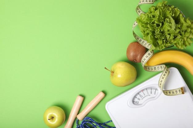 Miarka podłogowa i zdrowe produkty na kolorowym tle widok z góry
