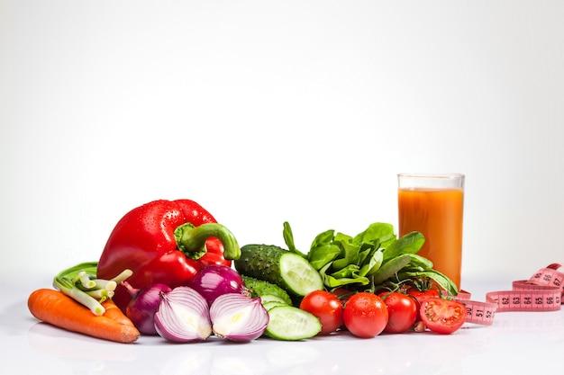 Miarka z pomidorami i warzywami na białym. pojęcie diety i zdrowego stylu życia
