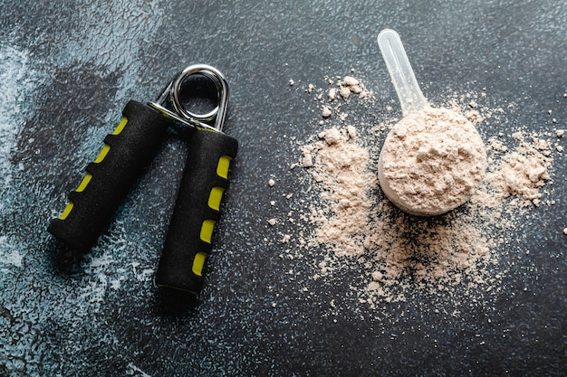 Miarki wypełnione proszkami białkowymi do odżywiania fitness, aby rozpocząć trening