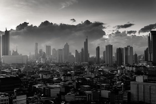 Miasto bangkok z wysokimi budynkami w centrum miasta i dramatycznym niebem o świcie. ton monochromatyczny