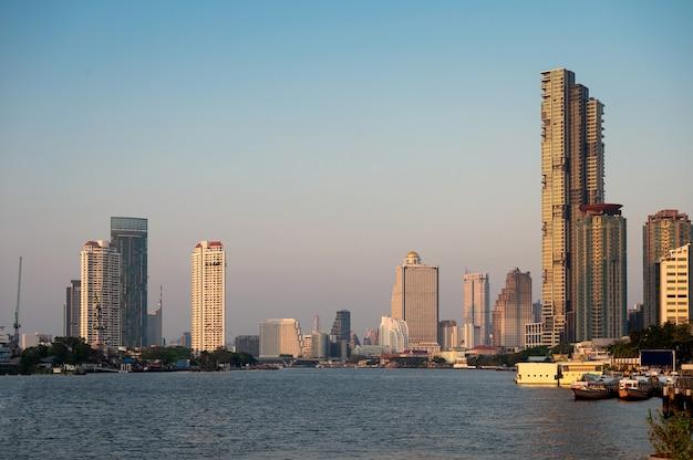 Miasto bangkok ze słońcem na wieżowcach w centrum miasta na chao phraya