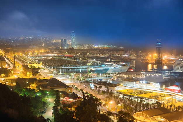 Miasto barcelona nocą. zobacz na port i pejzaż miejski z niebieskim ciemnym niebem