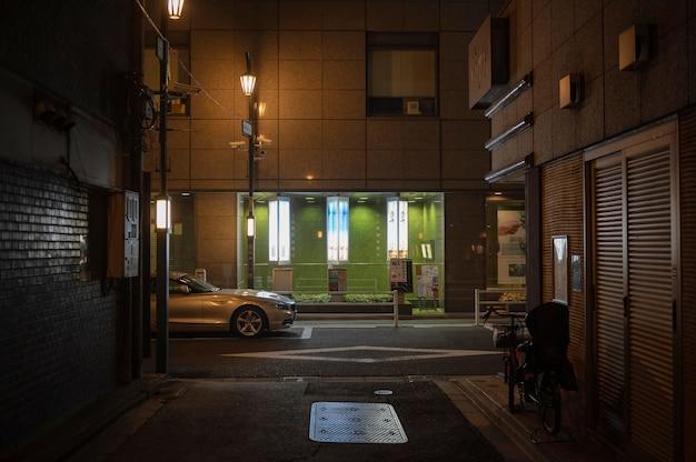 Miasto japonii nocą z samochodem na ulicy
