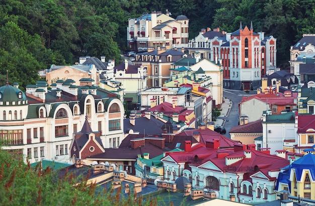 Miasto kijów. stare miasto. ukraina. piękny widok na starożytną ulicę andrzejki i kościół św. andrzeja wśród zielonych drzew na wzgórzu zamkowym w kijowie