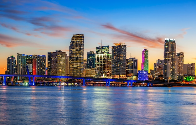 Miasto miami na florydzie, panorama zachodu słońca latem z kolorowymi oświetlonymi budynkami biznesowymi i mieszkalnymi oraz mostem w zatoce biscayne