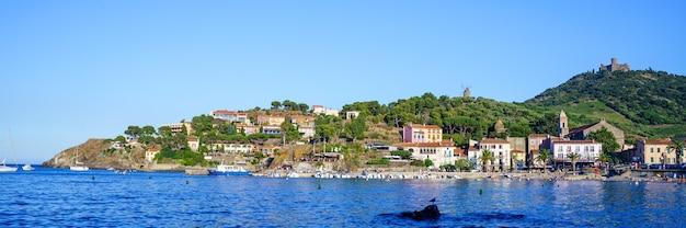 Miasto na wzgórzu z plażą i kościołem w średniowiecznym porcie z łodziami i ludźmi. koncepcja podróży