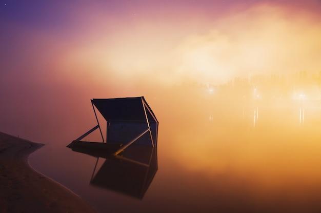 Miasto nocą, światła miasta odbite w wodzie, długi czas ekspozycji, mgła nad wodą, rzeka zalana, poziom wody w rzece wzrosła, sklep w wodzie