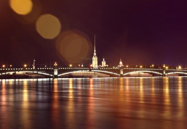 Miasto nocą widok na most trójcy i katedrę piotra i pawła w nocnych światłach