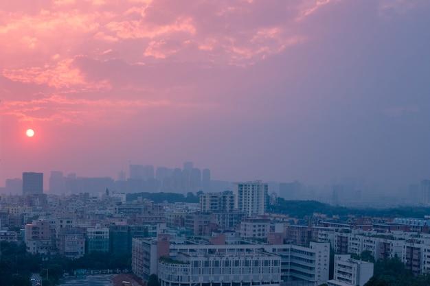 Miasto pod zachmurzonym niebem podczas różowego zachodu słońca wieczorem