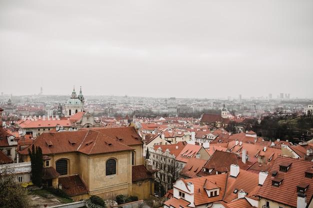 Miasto praga z czerwonymi dachami i kościół we mgle. widok na stare miasto w pradze. tonowanie w rustykalnym szarym kolorze