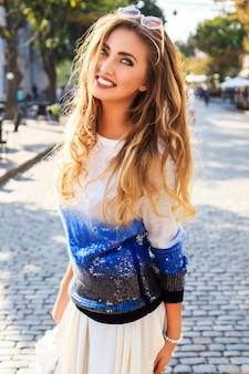 Miasto stylowy portret pięknej kobiety pozowanie na ulicy mrówka ładny słoneczny jesień jesienny dzień. noszenie jasnoniebieskiego swobodnego swetra i okularów przeciwsłonecznych.