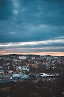 Miasto z wieżowcami pod niebieskim pochmurnym niebem