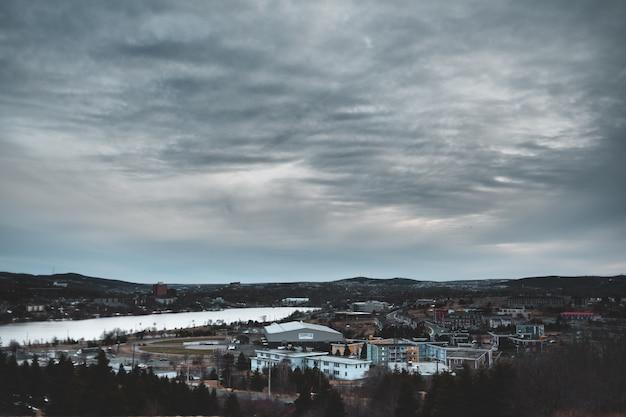 Miasto z wieżowcami pod szarymi chmurami w nocy
