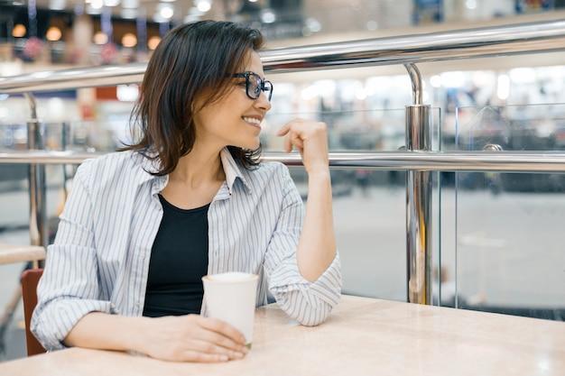 Miastowy portret jest ubranym szkła z filiżanką kawy kobieta