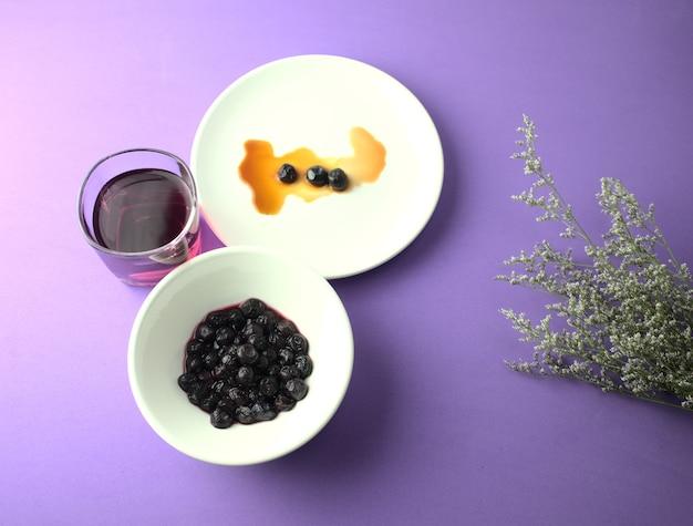 Miąższ jagód w soku z syropu na fioletowym tle z kwiatami jedzenie w płaskiej kuchni