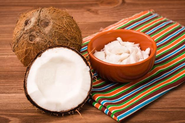 Miąższ kokosa w misce i kokosy na drewnianym stole