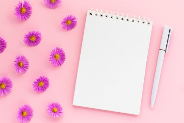 Michaelmas daisy pąki i pusty notatnik z piórem na różowo