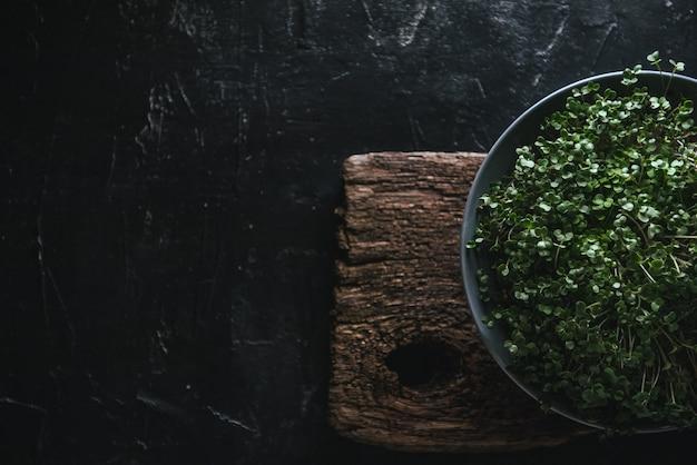 Microgreen w szarym naczyniu na drewnianym rustykalnym