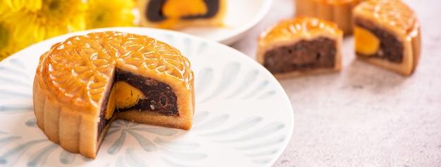Mid-autumn festival tradycyjna koncepcja żywności-piękne wycięte ciasto księżycowe na niebieskim talerzu wzór na białym tle z kwiatem, zbliżenie, kopia przestrzeń