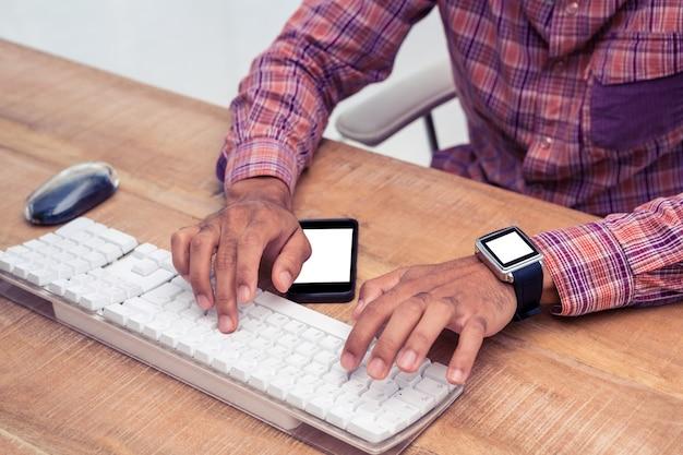 Midsection biznesmen pisać na maszynie na komputerowej klawiaturze na biurku w biurze