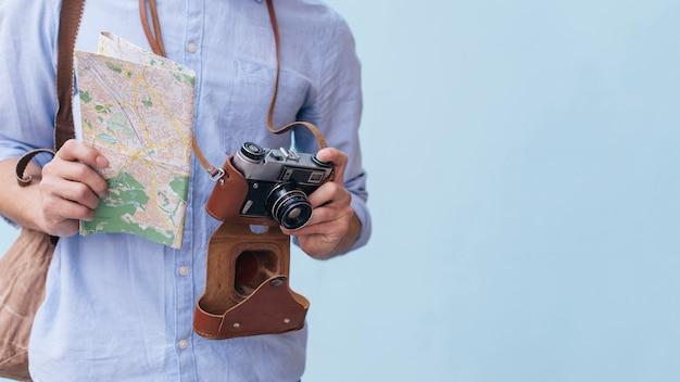 Midsection męski podróżnika fotograf trzyma kamerę i mapy pozycję przeciw błękitnemu tłu