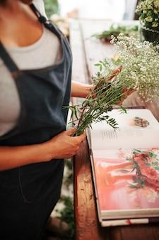 Midsection widok kobiety ręka trzyma wiązkę kwiaty z albumem fotograficznym na biurku