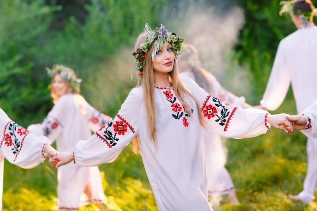 Midsummer, grupa młodych ludzi o słowiańskim wyglądzie podczas uroczystości przesilenia letniego.