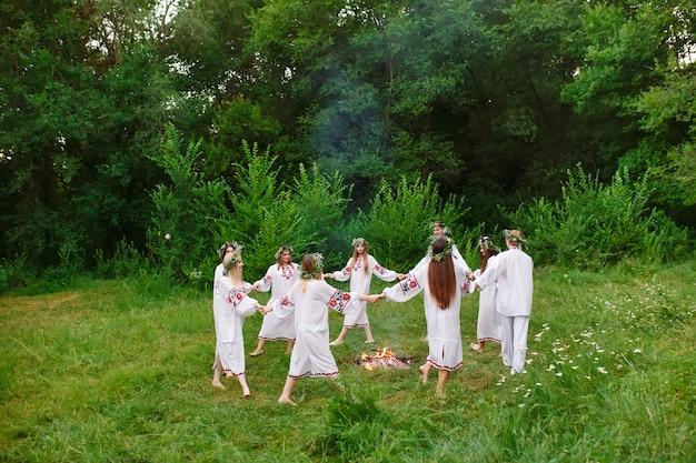 Midsummer, młodzi ludzie w słowiańskich ubraniach obracają się wokół pożaru w środku lata,.